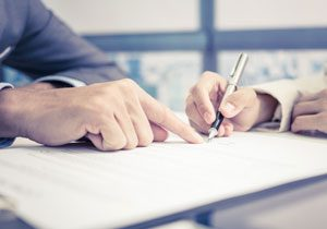 Trusts and Taxes, photo of people signing a document